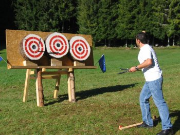 The athlete Francesco Martini throws his knives at the targets in the idyllic championship setting.